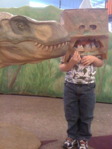 Paper bag mask vs. museum's baby T Rex